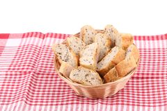 Wicker basket with bread slices on tablecloth. Stock Image