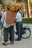 Wicker Basket Carried over the Shoulder of Countryman. Wicker Basket Filled with Sheafs of wheat and Flowers Carried over the Shoulder of Countryman and Old Man Royalty Free Stock Photo