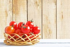 Wicker basket with cherry tomato on wooden table on background of wooden wall. Side view. Copy space. Concept of vegetarian food stock photo