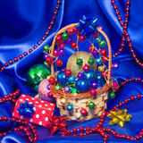 Wicker basket with Christmas decorations and gift. Wicker basket filled with Christmas decorations and gift box surrounded by Christmas balls and beads on blue stock photography
