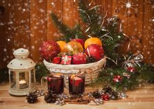 Wicker basket with Christmas toys and fruits, glasses of mulled wine and lantern. On wooden table stock photos