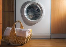 Wicker Basket with Clean Towels on the Floor by the Washing Machine with Laundry. House Interior Laundry Room. Wood Interior. Design royalty free stock photography