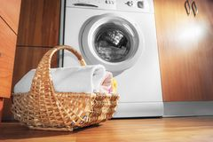 Wicker Basket with Clean Towels on the Floor by the Washing Machine with Laundry. House Interior Laundry Room. Wood Interior. Design stock photo