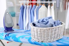 Wicker basket with clothes on ironing board. At dry-cleaner`s stock photography