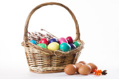 Wicker basket with colored eggs and willow branches on a white background Stock Photos
