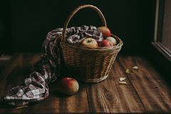 Wicker basket with the gifts of summer apples. Wicker basket with colorful apples covered with a cloth in a cage on a wooden rural background stock photography