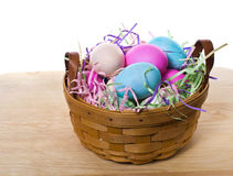 Wicker basket of colorful eggs Stock Image