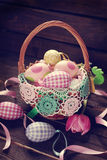Wicker basket with colorful eggs for easter Stock Photography