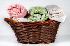 Wicker basket containing hand towels of different colors and patterns Stock Image