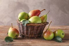 Wicker basket and delicious ripe pears. On table Stock Images