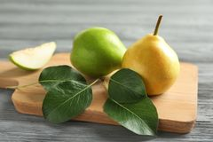 Wicker basket and delicious ripe pears. On table Stock Image