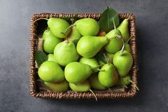 Wicker basket with delicious ripe pears. On grey background Royalty Free Stock Photography