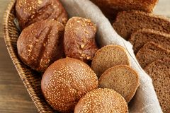 Wicker basket with different buns. On table Royalty Free Stock Photos
