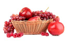 Wicker basket with different red fruits and berries. On white background royalty free stock photo