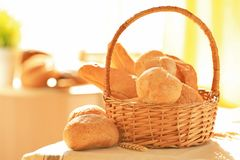Wicker basket with different types of fresh bread. On table Royalty Free Stock Image