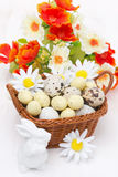 Wicker basket with easter eggs, flowers and white rabbit Royalty Free Stock Photography