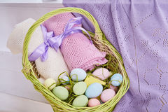 Wicker basket Easter set with colored eggs hay crocheted blankets covered with silk satin ribbon easter holy celebration, happy.  Stock Photography