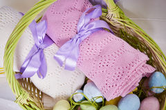 Wicker basket Easter set with colored eggs hay crocheted blankets covered with silk satin ribbon easter holy celebration, happy.  Stock Images