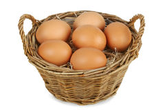 Wicker basket with eggs. Wicker basket with six brown eggs. Isolated on white. Clipping path included Stock Image