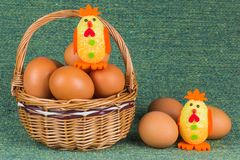 Wicker basket with eggs and chickens Stock Photos