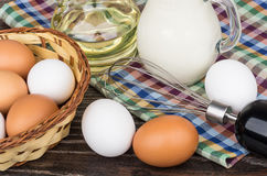 Wicker basket with eggs, vegetable oil, milk jug and whisk Royalty Free Stock Image