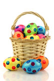 Wicker basket filled with colorful easter eggs Stock Photos