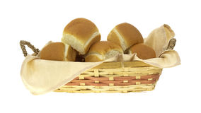 Wicker basket filled with dinner rolls. Side view of a colorful wicker basket filled with dinner rolls and napkin royalty free stock photography