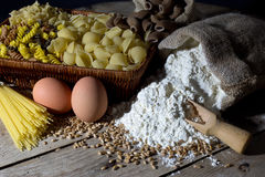 Wicker Basket Filled with Pasta of Different Colors and Shapes, Flour in Jute Bag and Two Eggs on Rustic Wooden Table Royalty Free Stock Photos