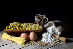 Wicker Basket Filled with Pasta of Different Colors and Shapes, Flour in Jute Bag and Two Eggs on Wooden Table On Black Stock Photography