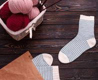 Wicker basket filled with wool and yarn with striped white socks on a dark wooden background Royalty Free Stock Photo