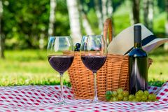 Wicker basket with food and wine to spend time. In the park on a picnic Stock Photo