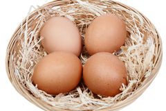 Wicker basket with four eggs on straw Royalty Free Stock Photos