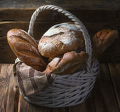 Wicker basket with fresh bread on a wooden table.  royalty free stock photography