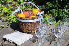 Wicker basket of fresh fruits, tablecloth and empty wine glasses. Wicker basket of fresh fruits on a bench in the green, next to the tablecloth and empty wine royalty free stock image
