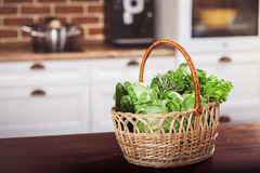 Wicker basket with fresh raw green vegetables at the brown wooden table on a kitchen. Ingredients for vegan salad Stock Photos