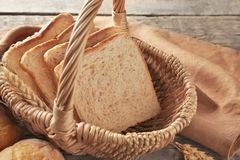 Wicker basket with fresh sliced bread and buns. On wooden table Royalty Free Stock Photo