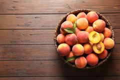 Wicker basket with fresh sweet peaches on wooden table. Top view royalty free stock photos