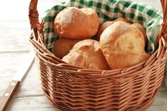 Wicker basket with fresh tasty buns. On table Royalty Free Stock Photography
