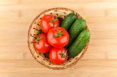 Wicker basket with fresh tomatoes and cucumbers isolated on boar Stock Image