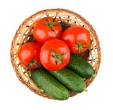 Wicker basket with fresh tomatoes and cucumbers isolated on whit Royalty Free Stock Image