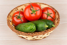Wicker basket with fresh tomatoes and cucumbers on table Royalty Free Stock Photography