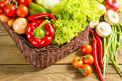 Wicker basket with fruits and vegetables on wooden table Stock Photo