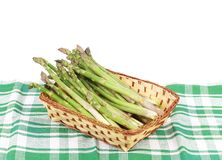 Wicker basket full with asparagus. Isolated on a white background stock images