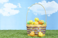 Wicker basket full of colorful easter eggs Royalty Free Stock Photography