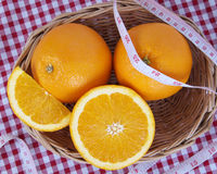 A wicker basket full of fresh orange fruits with centimeter Stock Images