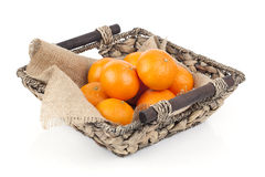 Wicker basket full of fresh orange fruits stock photo