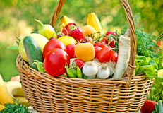 Wicker basket full of fruits and vegetables. Fresh organic fruits and vegetables on a table in wicker basket stock photography