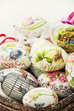 Wicker basket full of various painted Easter eggs Stock Photo