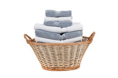 Wicker basket full of white and gray towels Royalty Free Stock Photos
