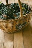 Wicker basket full of wine grapes. With the word home written on cloth stock images
